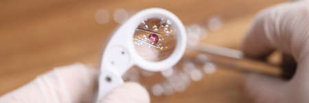 Photo pour Close-up view of person looking on pink diamond through magnifying loupe. Professional in protective gloves working with precious stone. Luxury jewelry concept - image libre de droit