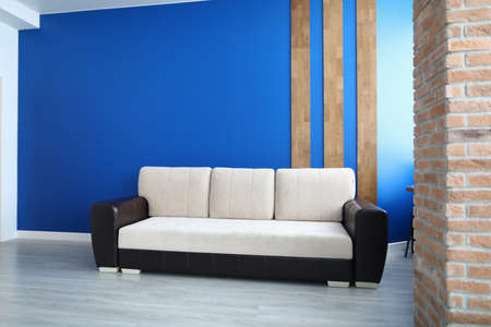 Photo pour Close-up of comfy sofa for office or living room. Stylish white colour and black insert. Bright blue wall with wooden lines decoration. Laminate on floor. Comfort and trendy interior design concept - image libre de droit