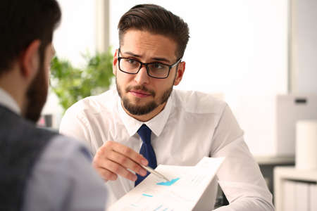 Photo pour Young handsome male colleagues with pen are discussing company project printed on paper at desk - image libre de droit