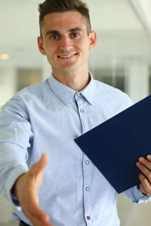 Photo pour Waist up portrait of smiling male in shirt standing and holding folder while giving hand for greeting - image libre de droit
