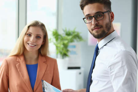 Photo pour Portrait of smiling bearded male with tie and jolly female as they are standing and discussing financial chart - image libre de droit
