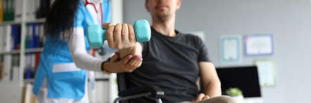 Photo pour Man on wheelchair holds dumbbell in his hands. Doctor and young man in wheelchair. Treatment and restoration lost functions. Rehabilitation after injuries. Restoration motor functions hand - image libre de droit