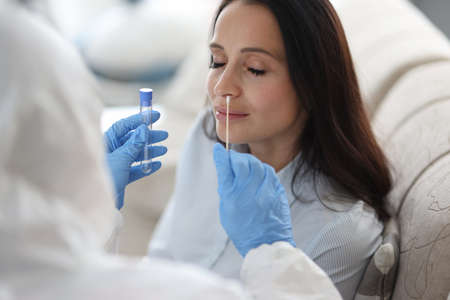 Photo pour Doctor laboratory assistant in protective suit takes swab from nose of sick patient at home. Laboratory tests for coronavirus concept. - image libre de droit