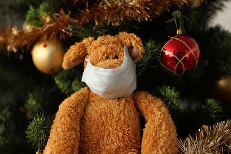 Photo pour Soft toy in protective mask on face hangs on Christmas tree at home close-up. Celebrating New Year in children with leukemia concept - image libre de droit