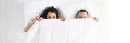 Top view of man and woman hiding under duvet. Happy funny couple laying together in bed. Lovely relationship in family. White bedding. Wake up and good morning concept