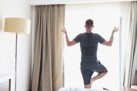 Foto de Man stands in lotus position by window. Morning exercise and relaxation concept - Imagen libre de derechos