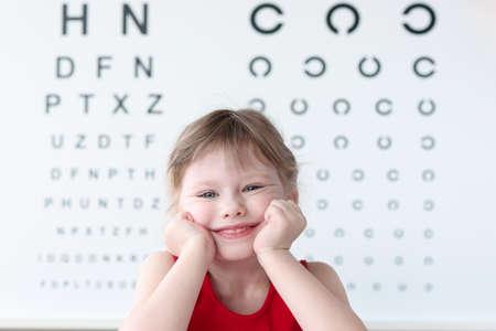 Photo pour Smiling little child against vision test table in medical clinic portrait. Health and happy childhood concept - image libre de droit