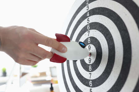 Photo for Rocket in hands of businessman hitting darts target closeup - Royalty Free Image