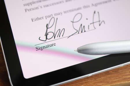 Photo pour Stylus writing signature on digital tablet closeup - image libre de droit