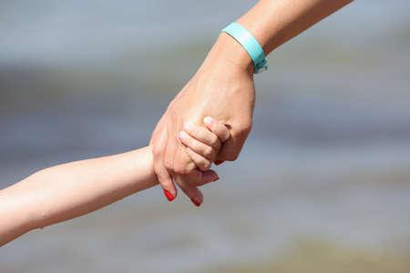 Photo pour Woman hand holds child hand. Parental support for young children - image libre de droit
