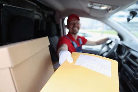 Foto de Man delivering yellow envelope from car closeup - Imagen libre de derechos