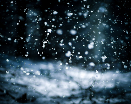 Detail of softly falling snowflakes in the nightly sky.