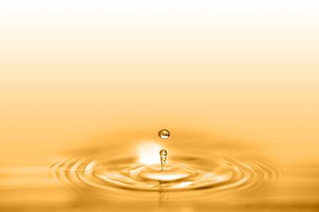 Foto de Closeup on drop of cosmetic golden oil liquid creating a circular wave. - Imagen libre de derechos