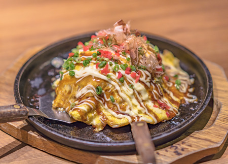 Foto de Japanese okonomiyaki covered with katsuobushi leek mayonnaise and bulldog sauce served on a hot plate with spatulas. - Imagen libre de derechos