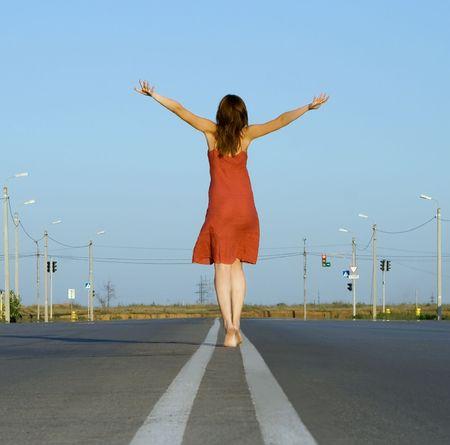 girl in red dress walk barefoot on empty road