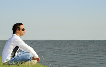 young caucasian man sitting alone and looking to the sea