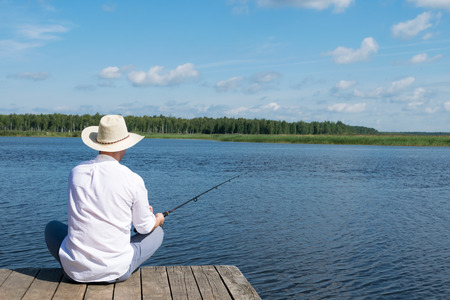 Photo pour a man in a hat sits on a pier with a fishing rod in his hands and looks at the river - image libre de droit