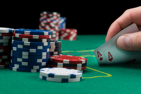 Foto de a poker player looks at his cards by lifting them on a green table poker chips are in the stack next to them - Imagen libre de derechos