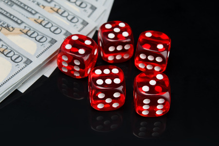 Photo pour on a black background with a reflection, five red dice for the game and hundred dollar bills laid out in a row - image libre de droit