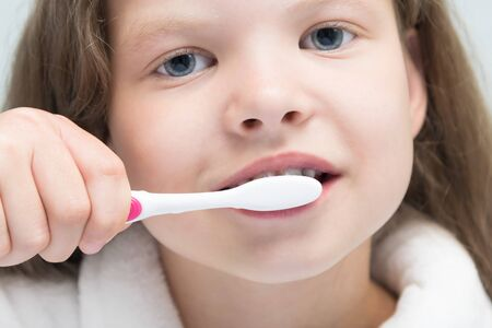 Photo pour girl brushing her teeth time of the morning toilet, close-up - image libre de droit