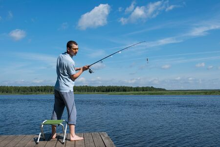 Photo pour man in sunglasses throws bait on a spinning in the lake for fishing - image libre de droit