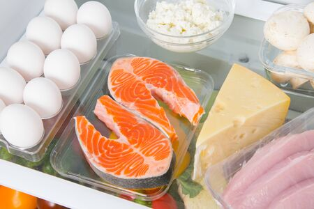 Foto de close-up shelf in the fridge where red fish, eggs, cheese, cottage cheese, mushrooms and meat - Imagen libre de derechos