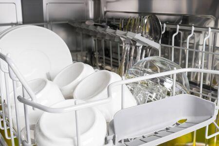 Foto de clean white dishes stand in the dishwasher, closeup background - Imagen libre de derechos