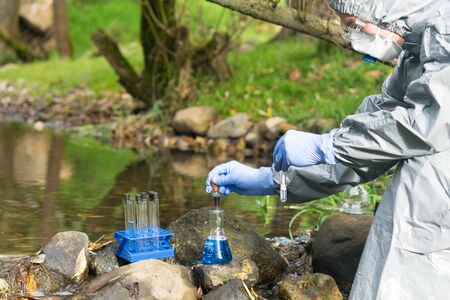 Foto de a man in a protective suit and respirator analyzes the water from the river in a portable laboratory using special reagents - Imagen libre de derechos