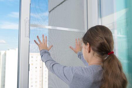 Foto de a dangerous situation, a child pushes a mosquito net out of the window, against the sky - Imagen libre de derechos