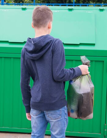 Foto de a boy in a blue jumper, carries a full bag of garbage to a container to throw it away, rear view - Imagen libre de derechos