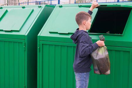 Foto de a boy in a blue jumper throws a full bag of garbage into a green container - Imagen libre de derechos