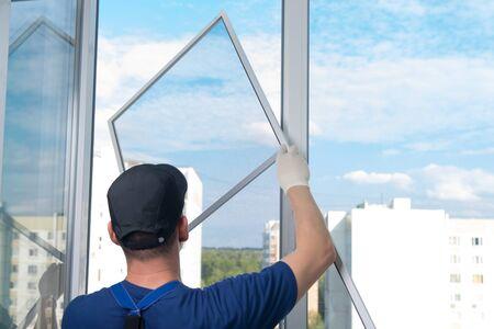 Photo pour a worker in a blue uniform, rear view, installs a mosquito net in a plastic window frame, against the sky - image libre de droit