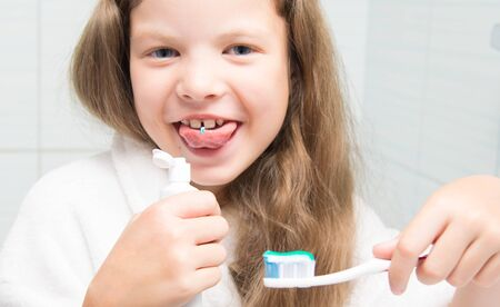 Photo pour close-up, a girl with long hair, holding a toothbrush in her hand and fooling around, trying to taste the paste - image libre de droit