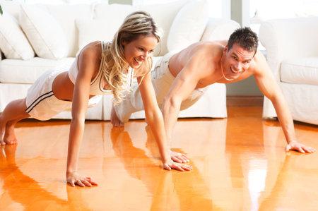 Foto de Young man and woman woman doing exercise  in the sunny room\r - Imagen libre de derechos