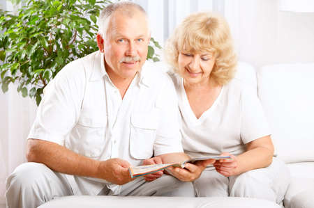 Happy smiling elderly couple reading a magazine  at home