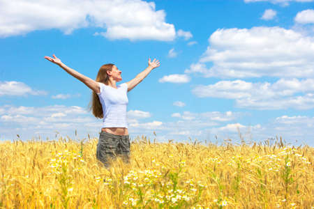 Photo for Happy young woman in the field under blue sky  - Royalty Free Image