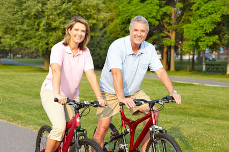 Happy elderly seniors couple biking in park