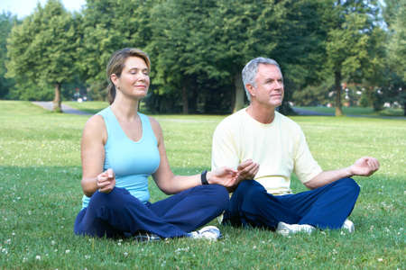 Happy elderly seniors couple doing yoga in park