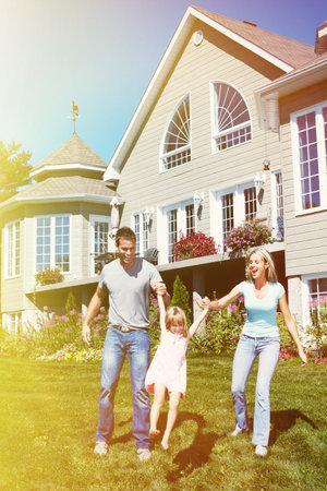 Foto de Happy smiling family with child over  house background - Imagen libre de derechos