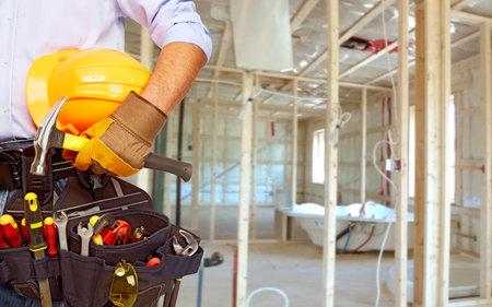 Photo pour Worker with a diy tool belt over construction background - image libre de droit