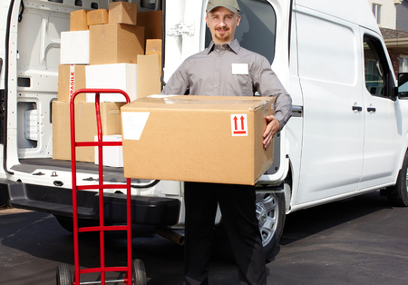 Photo for Young delivery man with parcel near cargo truck. Shipping service. - Royalty Free Image