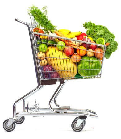 Foto de Grocery shopping cart with vegetables and fruits. Isolated on white. - Imagen libre de derechos