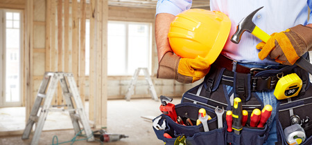 Foto de Builder handyman with construction tools. House renovation background. - Imagen libre de derechos