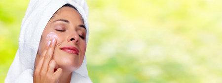 Photo pour Beautiful woman face with moisturising cream. Skin care background. - image libre de droit