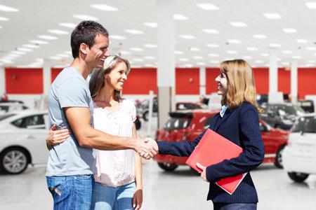 Photo pour Young couple with a car dealer. Auto dealership and rental concept background. - image libre de droit