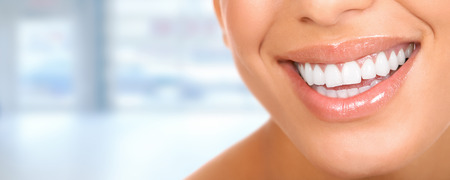 Photo pour Smiling woman mouth with great teeth. Over blue background - image libre de droit