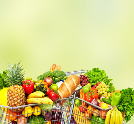 Foto für Grocery shopping cart with fruits and vegetables over green background. - Lizenzfreies Bild