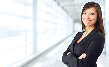 Foto de Beautiful chinese business woman over blue office background. - Imagen libre de derechos