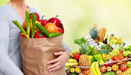 Foto de Young woman near shopping cart with fruits and vegetables over green background. - Imagen libre de derechos