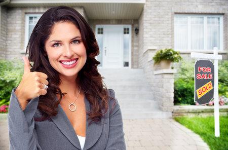 Foto de Real Estate agent woman near new house. Home for sale concept. - Imagen libre de derechos